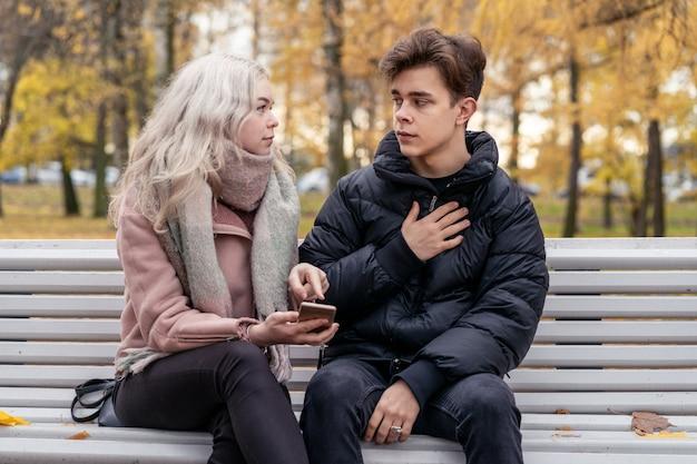 Het jonge mooie blondemeisje beschuldigt haar vriend door vinger op het telefoonscherm te richten