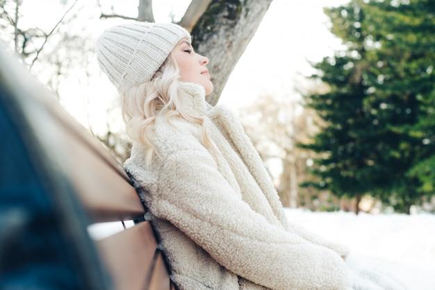 Het jonge mooie blondemeisje zit op een bank in het park in de winter