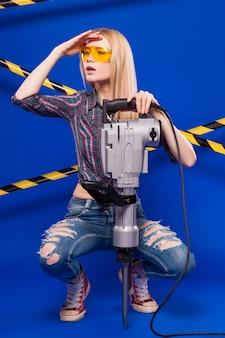 Het jonge mooie bouwersmeisje in geruit overhemd, jeans en glazen houdt puncher