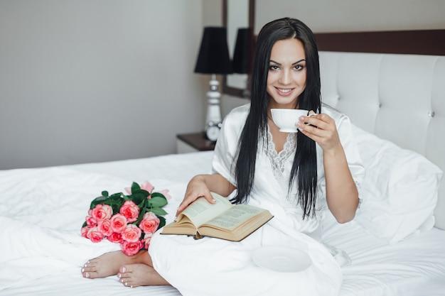 Het jonge mooie brunette gelukkige meisje zit in haar bed met een boeket rozen, drinkt koffie en leest 's ochtends een boek.