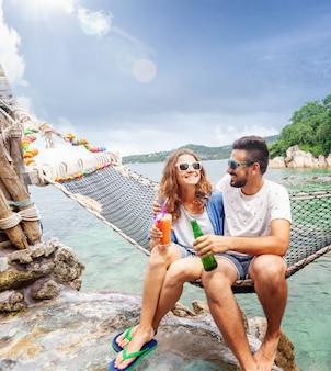 Het jonge mooie gelukkige glimlachende grappige paar een man en een vrouwen beste vrienden op een hangmat op vakantie drinkt verfrissende dranken