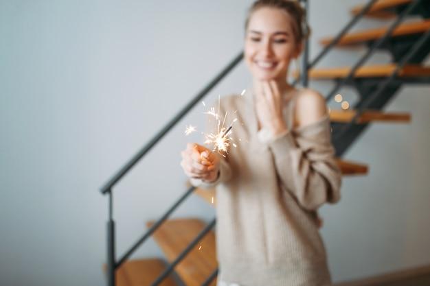 Het jonge mooie gelukkige meisje met blondehaar in zijdekleding en comfortabel beige cardigan houdt de sterretjes thuis, selectieve nadruk
