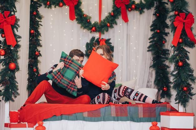 Het jonge mooie gelukkige paar stellen op studio. modellen knuffelen, stijlvolle winterkleding dragen.