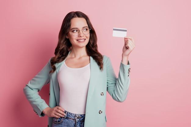 Het jonge mooie glimlachende meisje dat creditcard toont, kijkt naar de lege ruimte
