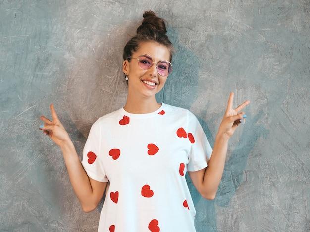 Het jonge mooie glimlachende vrouw kijken. trendy meisje in casual witte zomerjurk en zonnebril. . toont vredesteken