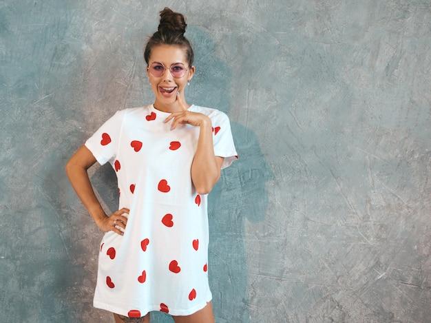 Het jonge mooie glimlachende vrouw kijken. trendy meisje in casual witte zomerjurk en zonnebril.