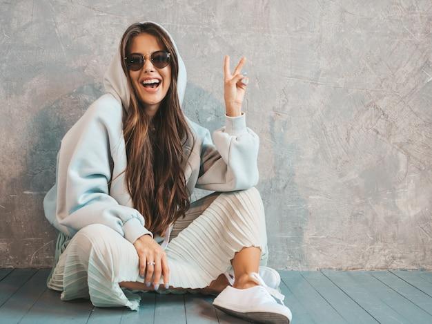 Het jonge mooie glimlachende vrouw kijken. trendy meisje in casual zomer hoodie en rok kleding. grappig en positief wijfje in zonnebril die op de vloer zitten en vredesteken tonen
