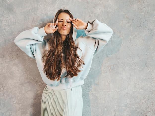 Het jonge mooie glimlachende vrouw kijken. trendy meisje in casual zomer hoodie en rok kleding. . haar tong laten zien
