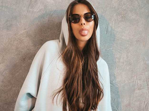 Het jonge mooie glimlachende vrouw kijken. trendy meisje in casual zomer hoodie en rok kleding. in zonnebril. toont tong