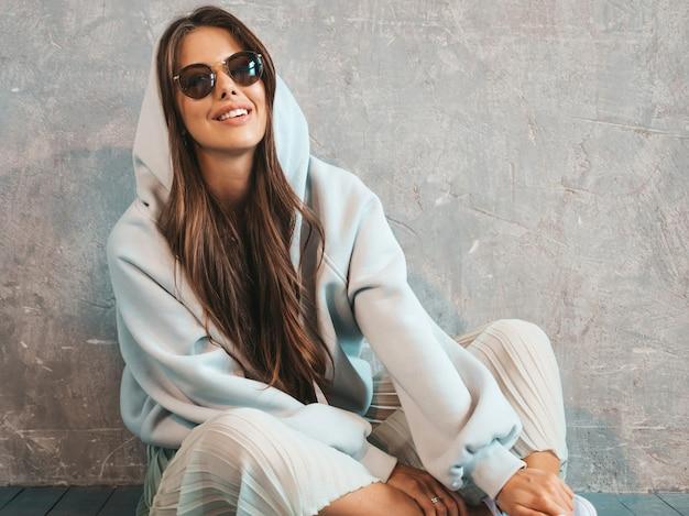 Het jonge mooie glimlachende vrouw kijken. trendy meisje in casual zomer hoodie en rok kleding. op de vloer zitten