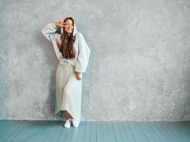 Het jonge mooie glimlachende vrouw kijken. trendy meisje in casual zomer hoodie en rok kleding. . toont vredesteken