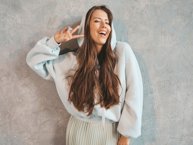 Het jonge mooie glimlachende vrouw kijken. trendy meisje in casual zomer hoodie en rok kleding. . vredesteken tonen
