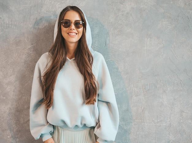 Het jonge mooie glimlachende vrouw kijken. trendy meisje in casual zomer hoodie en rok kleding.