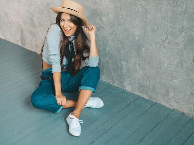 Het jonge mooie glimlachende vrouw kijken. trendy meisje in casual zomer kleding en hoed. op de vloer zitten
