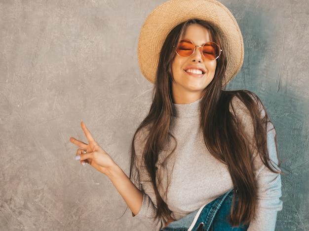 Het jonge mooie glimlachende vrouw kijken. trendy meisje in casual zomer overall kleding en hoed. toont vredesteken
