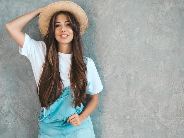 Het jonge mooie glimlachende vrouw kijken. trendy meisje in casual zomer overall kleding en hoed.