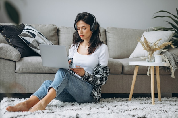 Het jonge mooie huis die van de vrouwenzitting aan laptop in oortelefoons werken