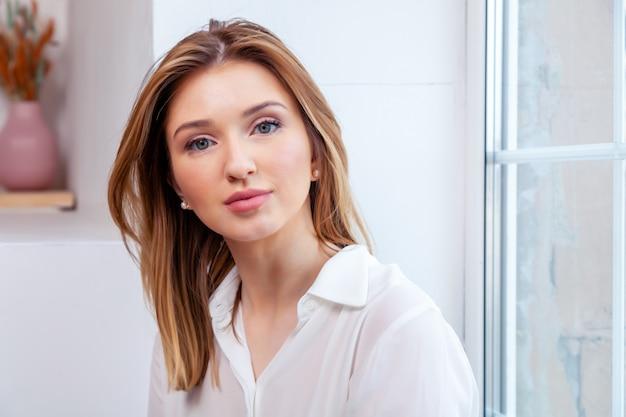 Het jonge mooie kaukasische meisje van het meisjes rode haar in wit overhemd, jeans die op venster zitten.