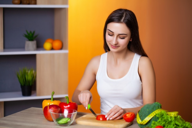 Het jonge mooie meisje bereidt een nuttige dieetsalade voor