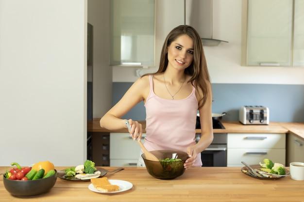 Het jonge mooie meisje bereidt gezonde natuurvoeding voor ontbijt voor.