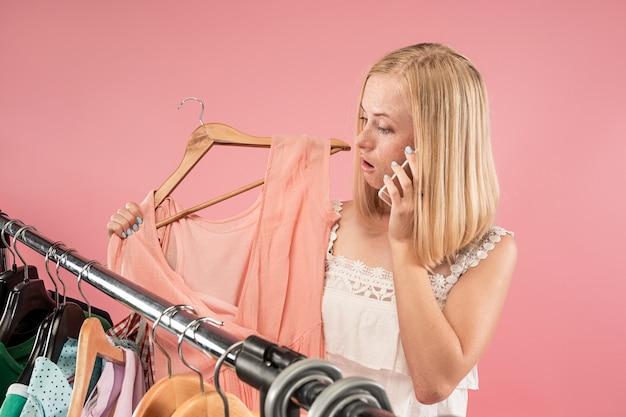 Het jonge mooie meisje dat jurken bekijkt en het probeert terwijl het kiezen bij winkel