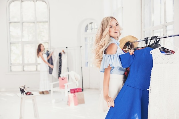 Het jonge mooie meisje dat jurken bij winkel kiest en past