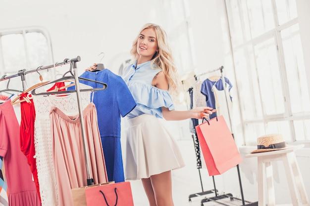 Het jonge mooie meisje die en kleding bij winkel kiezen proberen