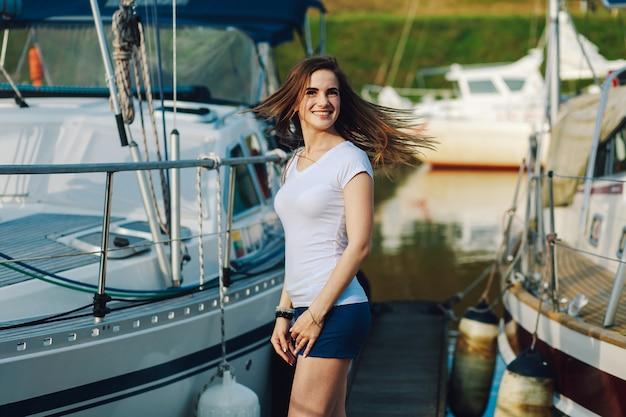 Het jonge mooie meisje glimlacht bij de camera op de achtergrond van de zomerjachten