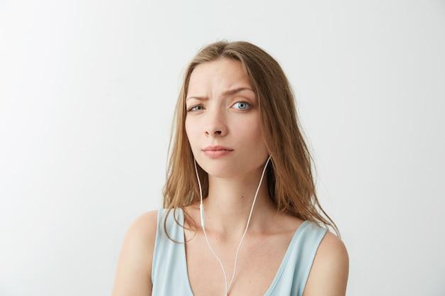 Het jonge mooie meisje heft brow op luisterend aan stromende muziek in hoofdtelefoons.