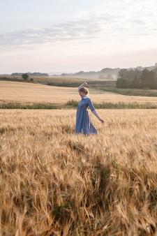 Het jonge mooie meisje in blauwe kleding met verzameld haar stelt