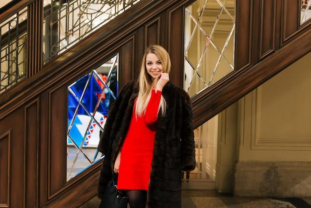 Het jonge mooie meisje in een nertsmantel in gom op rood vierkant winkelt, een binnenmarkt, moskva