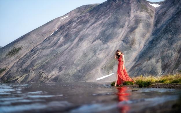 Het jonge mooie meisje in een rode kleding loopt en danst op de oceaan op de achtergrond van het strand en de rotsen