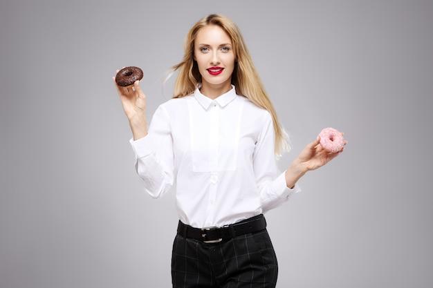 Het jonge mooie meisje in wit overhemd in studio houdt donuts in handen.