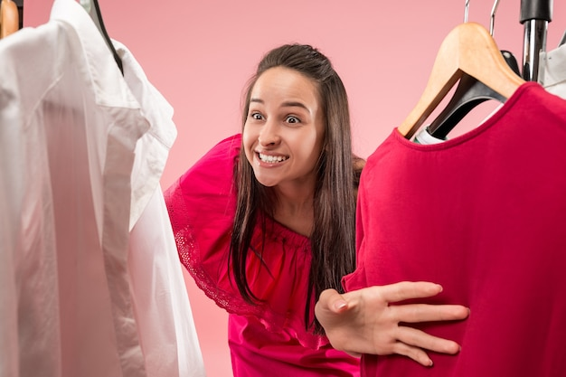 Het jonge mooie meisje kijkt naar jurken en probeert het tijdens het kiezen in de winkel