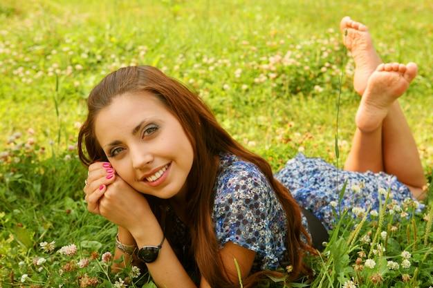 Het jonge mooie meisje legt op een gras