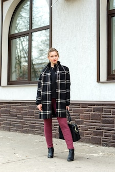 Het jonge mooie meisje met een modieuze zak bevindt zich op de straat