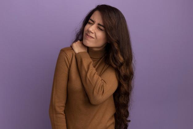 Het jonge mooie meisje met gesloten ogen die bruine coltrui dragen greep pijnlijke schouder die op purpere muur wordt geïsoleerd