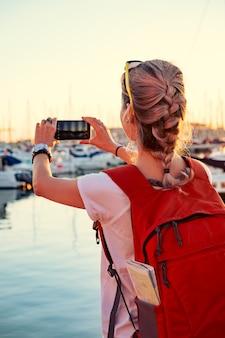 Het jonge mooie meisje neemt een foto van een baai met jachten bij zonsondergang
