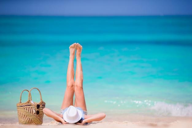 Het jonge mooie meisje ontspannen op wit strand. de toeristenvrouw geniet strand van vakantie liggend op het zand