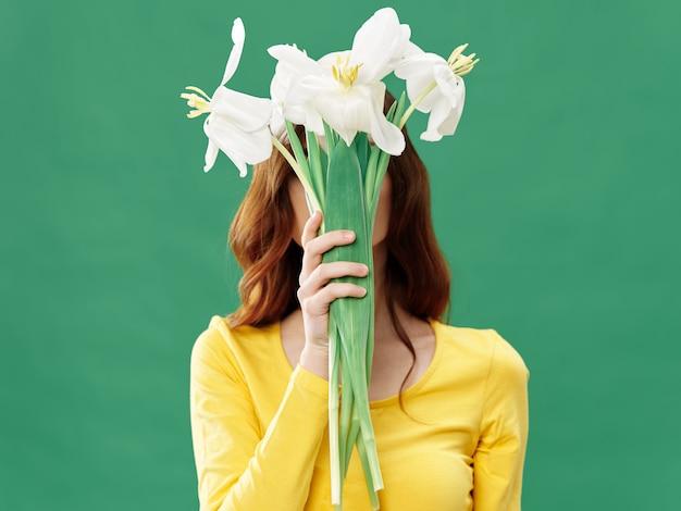 Het jonge mooie meisje van de lente met bloemen op een gekleurde ruimte, vrouw het stellen met een boeket van bloemen, vrouwendag