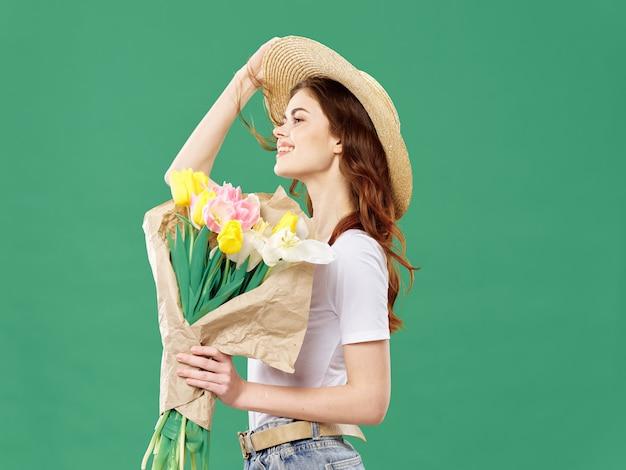 Het jonge mooie meisje van de lente met bloemen op een gekleurde studio. vrouw poseren met een boeket bloemen.