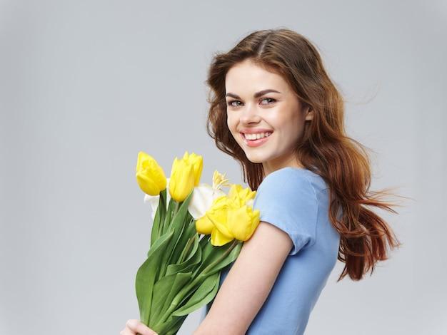 Het jonge mooie meisje van de lente met bloemen op een gekleurde studioachtergrond, vrouw het stellen met een boeket van bloemen, vrouwendag