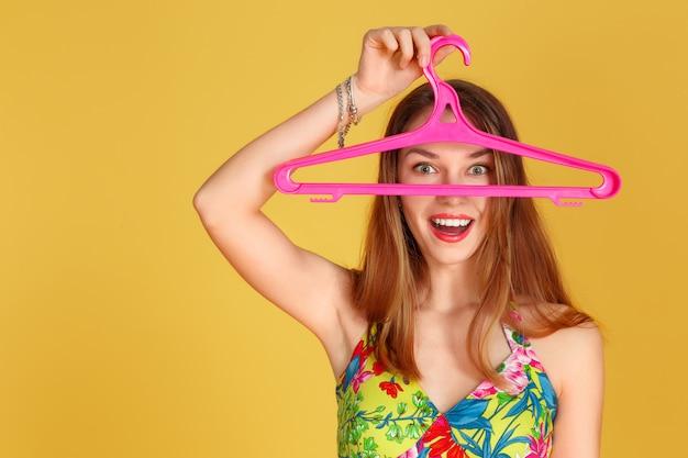 Het jonge mooie meisje verbergt haar gezicht achter een kleerhanger. op een gele achtergrond