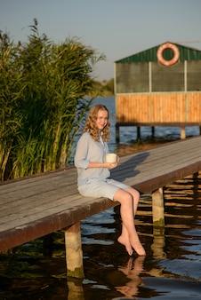 Het jonge mooie meisje zit op een pier aan de oever van het meer, met verlaagde benen in water