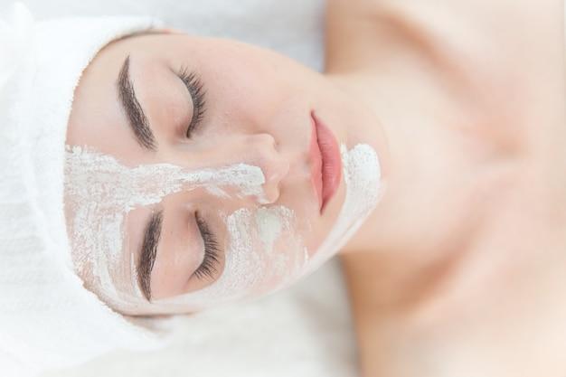 Het jonge mooie meisjesgezicht maskeren ontspannen in gesloten de ogen van de kuuroordsalon