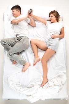 Het jonge mooie paar dat in een bed met wekker ligt