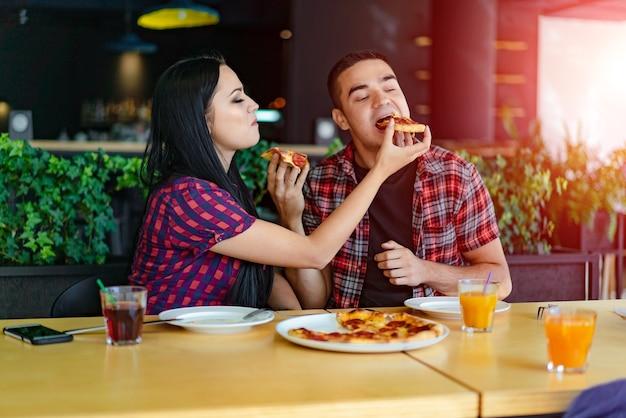 Het jonge mooie paar deelt pizza en eet het in pizzeria.