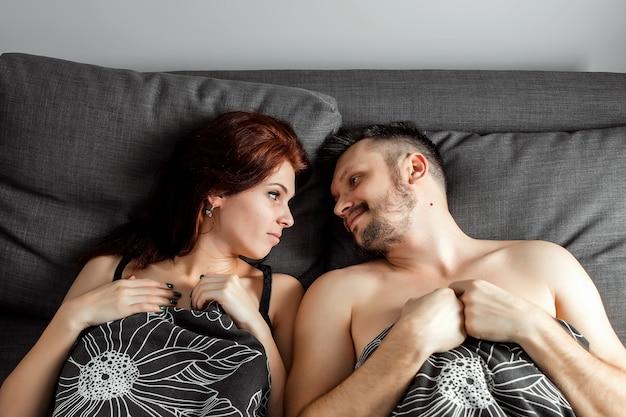 Het jonge mooie paar die in een bed liggen, gelukkige glimlachliefde die aan elkaar, bovenkant boven mening kijken, houdt de vorm van het handenhart