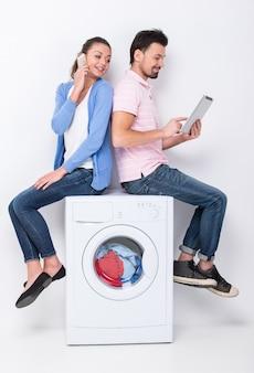 Het jonge mooie paar gebruikt laptop en mobiele telefoon.