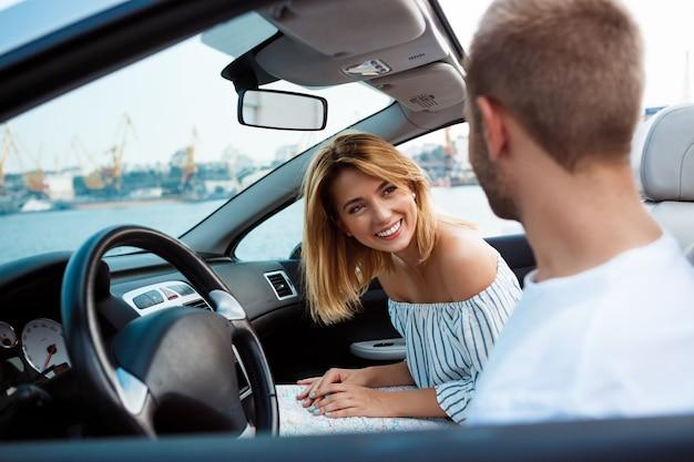 Het jonge mooie paar glimlachen, die in auto dichtbij overzees zitten.